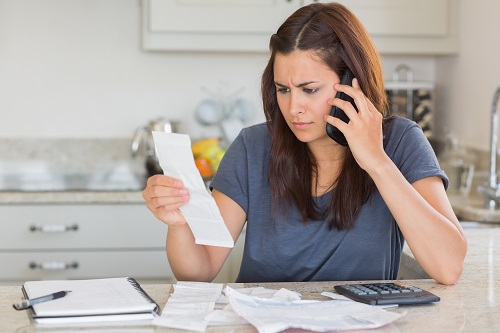 Woman calling while calculating bills in kitchen